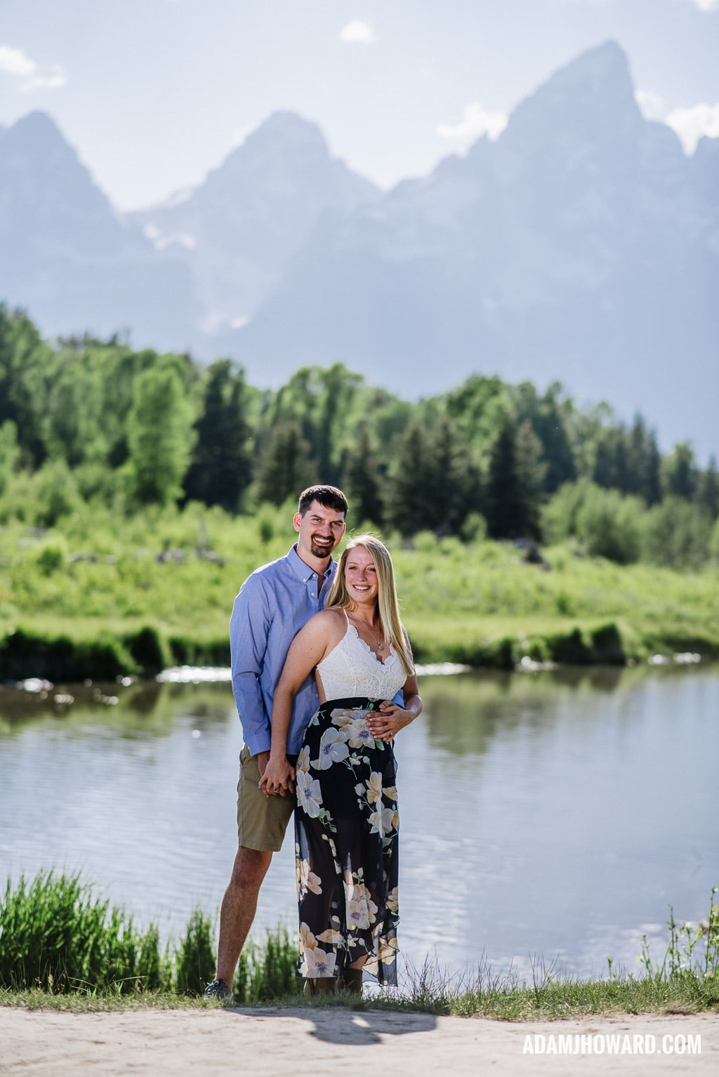 Happy couple hugging in front of the Tetons in the Summer